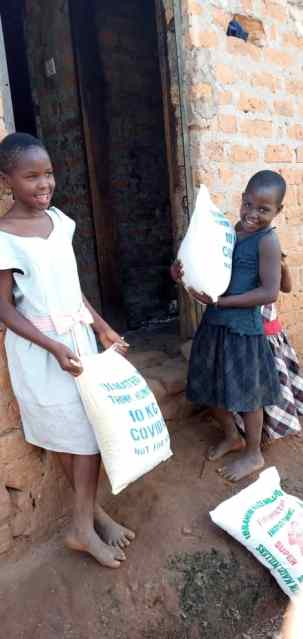 Nazziwa's sisters carrying food donated by Think Humanity hoima